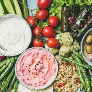 Healthy vegan snack set. Flat-lay of beetroot hummus, yogurt and herb dip, olives, flatbread, cous cous, dolma, vegetables and fruit on tray over marble background, top view. Clean eating food concept
